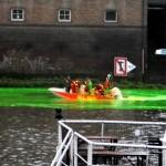 Der Künstler (in grün) beim Färben des Flusses